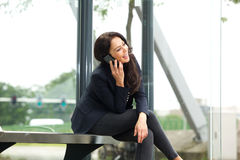 Smiling woman sitting at bus stop talking on mobile phone Royalty Free Stock Image