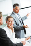 Smiling woman sitting at a business meeting with colleagues Royalty Free Stock Photos
