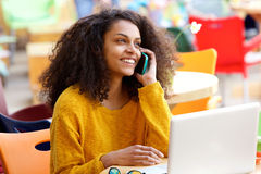 Smiling woman sitting at cafe and talking on mobile phone Royalty Free Stock Image