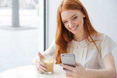Smiling woman sitting in cafe and using cell phone. Smiling pretty redhead young woman sitting in cafe and using cell phone Stock Photo
