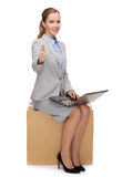 Smiling woman sitting on cardboard box with laptop Royalty Free Stock Image