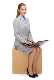 Smiling woman sitting on cardboard box with laptop Royalty Free Stock Images