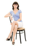 Smiling woman sitting on a chair Royalty Free Stock Photography