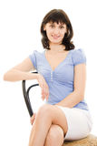 Smiling woman sitting on a chair Royalty Free Stock Photos
