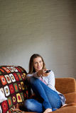Smiling woman sitting on comfortable sofa with remote control Royalty Free Stock Image