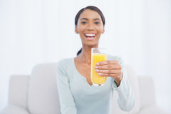 Smiling woman sitting on cosy sofa holding glass of orange juice Royalty Free Stock Photos