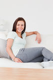 Smiling woman sitting on a couch Royalty Free Stock Photos
