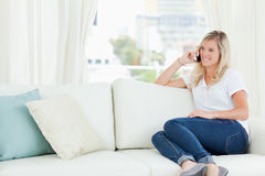 A smiling woman sitting on the couch as she talks on her phone Stock Photo