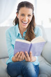Smiling woman sitting on couch holding book Royalty Free Stock Images