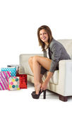 Smiling woman sitting on couch taking off her shoes Royalty Free Stock Image
