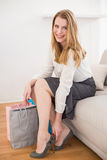 Smiling woman sitting on couch taking off her shoes. At home in the living room stock photography