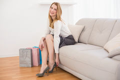 Smiling woman sitting on couch taking off her shoes. At home in the living room royalty free stock photo