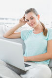 Smiling woman sitting on couch using her laptop Royalty Free Stock Photography
