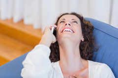 Smiling woman sitting on the couch and using her smartphone Royalty Free Stock Photography