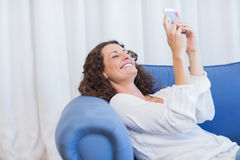Smiling woman sitting on the couch and using her smartphone Stock Images