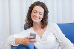 Smiling woman sitting on the couch and using her smartphone Royalty Free Stock Images