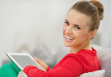 Smiling woman sitting on couch and using tablet pc Stock Photo