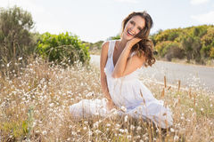 Smiling woman sitting on countryside landscape Royalty Free Stock Photography