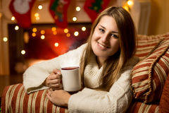 Smiling woman sitting with cup of hot tea at fireplace at Christ Royalty Free Stock Images