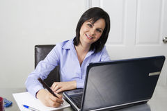 Smiling woman at laptop with pen and paper Stock Photography