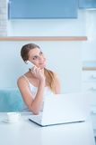 Smiling woman sitting at a desk taking call stock photos