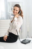Smiling woman sitting on desk and talking on the telephone Stock Images