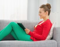 Smiling woman sitting on divan and using tablet pc Stock Images