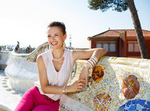Smiling woman sitting on the famous trencadis style bench. Get inspired by Park Guell in your next trip to Barcelona, Spain. Smiling young woman sitting on the Stock Images