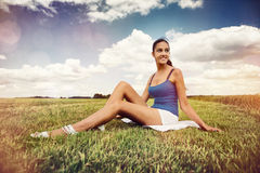 Smiling woman sitting in a field with sun flare Stock Photography