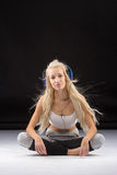 Smiling woman sitting on the floor in earphones Stock Image