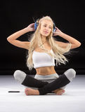 Smiling woman sitting on the floor in earphones Royalty Free Stock Image