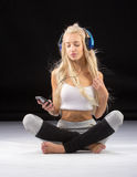 Smiling woman sitting on the floor in earphones Royalty Free Stock Photography