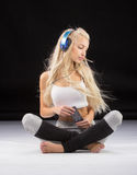 Smiling woman sitting on the floor in earphones Royalty Free Stock Images