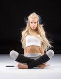 Smiling woman sitting on the floor in earphones Stock Photo