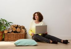 Smiling woman sitting on floor with laptop at home Royalty Free Stock Photo
