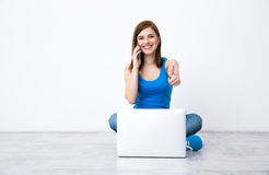 Smiling woman sitting on the floor with laptop Stock Photo