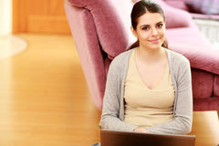 Smiling woman sitting on the floor with laptop Royalty Free Stock Photos