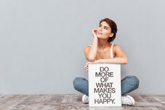 Smiling woman sitting on the floor with motivational board Stock Photos