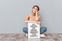 Smiling woman sitting on the floor with motivational board Stock Photo
