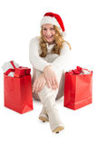 Smiling woman sitting on floor with shopping bag. On white background Royalty Free Stock Image