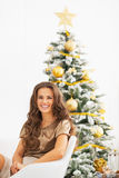 Smiling woman sitting in front of christmas tree Stock Photography