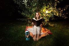 Smiling woman sitting on grass at night and reading big old book Stock Photography