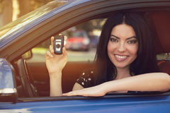 Smiling woman sitting in her new blue car showing keys Stock Photography