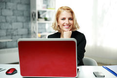 Smiling woman sitting at her workplace Stock Image