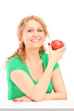 Smiling woman sitting and holding a red apple Royalty Free Stock Image