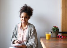 Smiling woman sitting at home with pen and paper Royalty Free Stock Photo