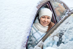 Smiling woman sitting inside of snow-covered car Stock Photos