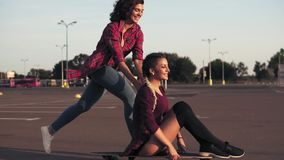 Smiling woman sitting on a longboard while her friend is pushing her behind and running during sunset. Enjoying life. Lens flare. Slowmotion shot stock footage