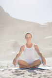 Smiling woman sitting in lotus pose on beach Stock Images