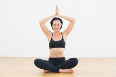 Smiling woman sitting in lotus pose at fitness studio Royalty Free Stock Image